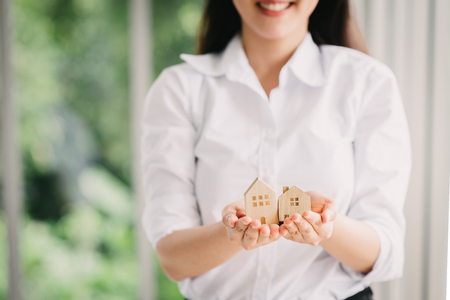 Happy woman present miniature wooden house. Property, mortgage and house insurance concept