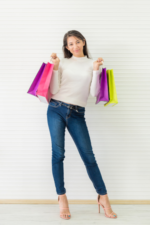 Happy woman with colorful shopping bag on white wall background