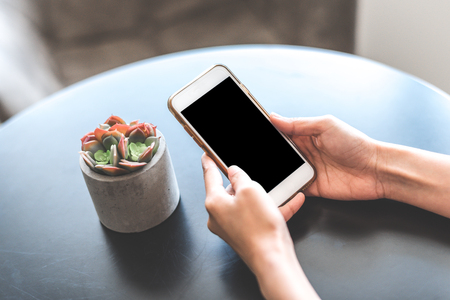 Hand using smartphone with blank screen on the table Banco de Imagens