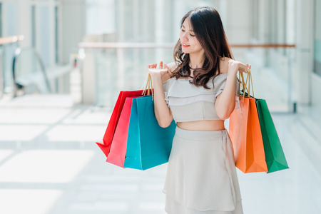 Happy Asian woman holding colorful shopping bags indoor Banco de Imagens