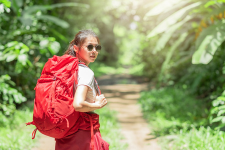 Asian woman traveler with backpack walking in forest.Adventure, travel people concept