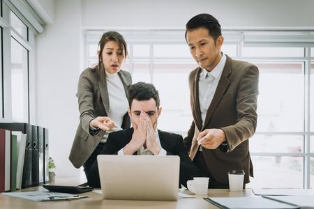 Business people blamimg depressed caucasian man colleague in office. Banco de Imagens