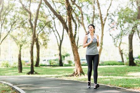 Mooie jonge gezonde Aziatische vrouw die in het park loopt