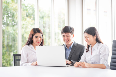 Group of young Asian business people smiling while looking at something on laptop screen in meeting room