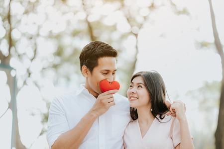 Gelukkig Aziatisch paar verliefd omarmen spelen met hart in de hand in het park Stockfoto