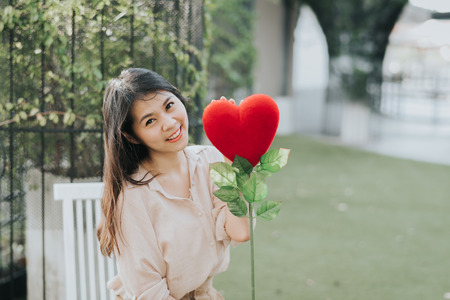 Happy Attractive young Asian woman holding red love hearts flower outdoor Banco de Imagens