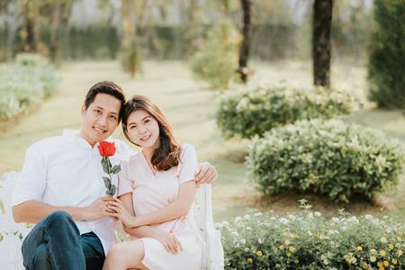 Coppia asiatica innamorata che si abbraccia con la rosa nel parco