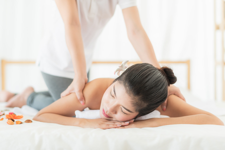 Beautiful Asian woman relaxing while getting massage in spa salon