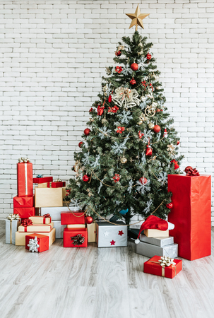 Christmas tree with gift box on white brick wall background