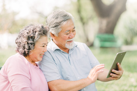 Happy senior Asian couple using digital tablet while sitting in the park 스톡 콘텐츠