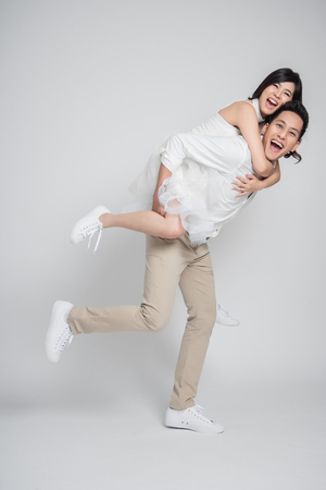 Happy Asian groom gives a bride piggyback ride on white background. Banque d'images