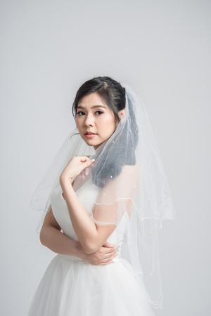 Hermoso retrato de novia con velo sobre fondo blanco.