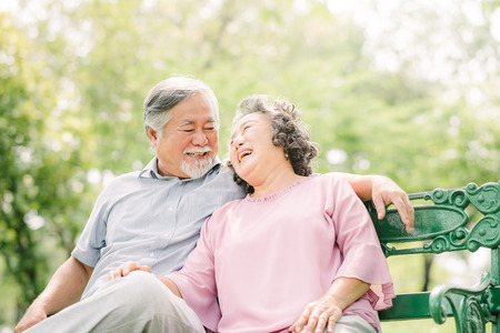 Happy Asian Senior couple laughing while sitting on the bench in the park 스톡 콘텐츠