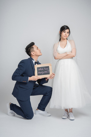 Asian man down on his knee and hold will you marry me? sign to ask his girlfriend on white background