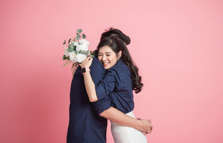 Happy Asian woman hugging her boyfrienfd with bouquet in hand on pink background