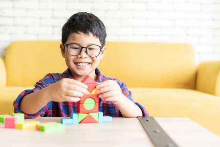 Happy young Asian boy playing with colorful building block