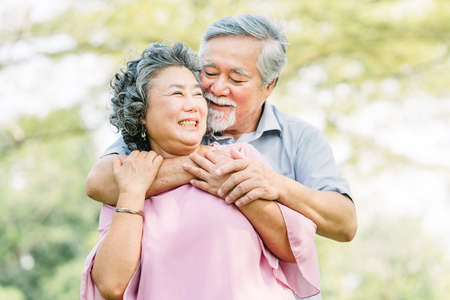 Happy Asian senior couple in love laughing while holding each other tightly outdoor in the park 스톡 콘텐츠
