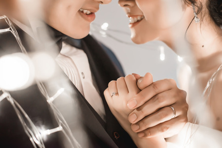 Cropped shot of bride and groom holding hand in fairy light. Focus on the ring. 스톡 콘텐츠