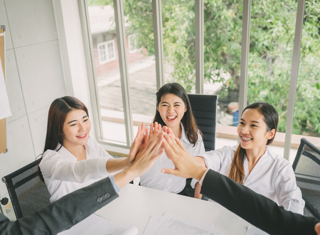 Group of young Asian business people give high five to celebrate success after finised meeting on new project