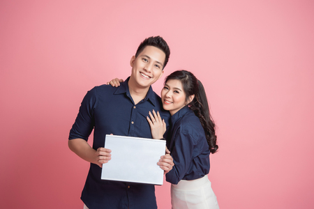 Happy young Asian couple holding blank banner isolated on pink background