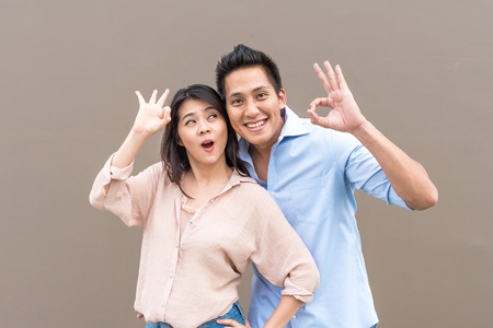 Happy Asian couple feeling excited and smiling with ok hand gesture