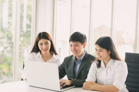 Group of young Asian business people working on project in laptop in meeting room