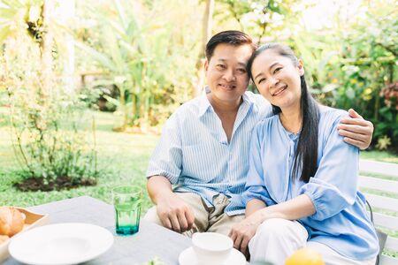 Happy senior Asian couple hugging outdoor in garden in morning Stock Photo