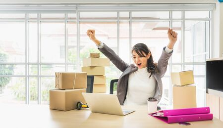 Happy successful business woman with arms up working with laptop and cardboard box on table in home office. business online and delivery concept. 写真素材