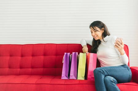 Happy woman looking in shopping bags with mobile smartphone in hand whlie sitting on red sofa. Shopping online concept. Foto de archivo - 125287613