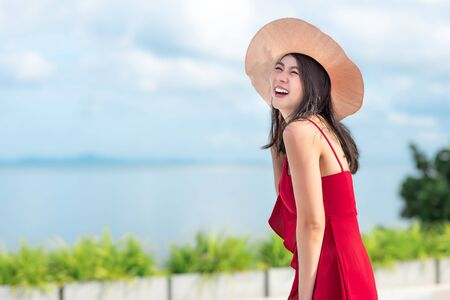 Happy attractive young Asian woman in red dress with hat enjoys her vacation in sunny day in summer at resort 写真素材