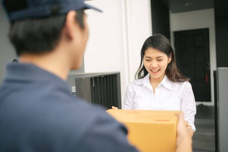 Happy Asian woman received cardboard package from delivery man in front of her home 写真素材