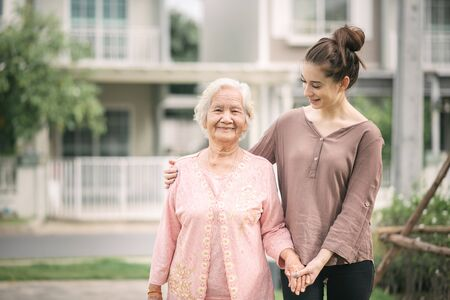 Happy Caucasian woman walking and embracing Asian elderly woman outdoor in home garden Foto de archivo - 125287617