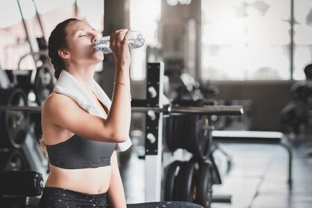 Young Caucasian woman drinking water from bottle after workout in fitness gym 写真素材