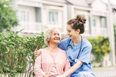 Happy nurse caregiver laughing with Asian elderly woman outdoor