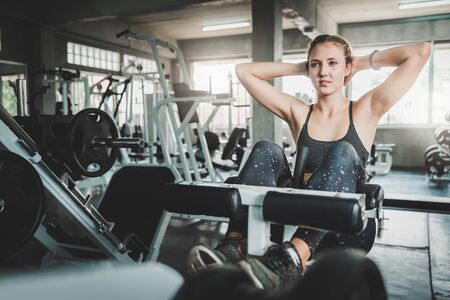 Young Caucasian woman doing decline bench crunch sit up in fitness gym. Abdominal exercises