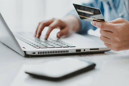 Hand holding credit card while using latop for online shopping or make a payment online