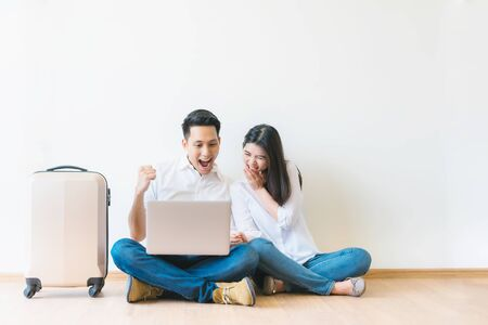 Asian couple with laptop celebrating successful planning vacation travel trip with luggage standing nearby Foto de archivo - 127528644