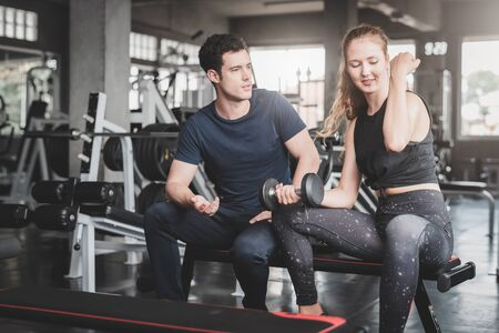 Caucasian couple discussing workout progress on bench in fitness gym