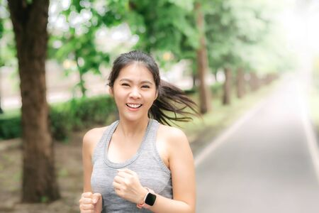 Beautiful young healthy Asian woman running in the park in the morning