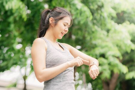 Happy Asian woman checking smartwatch before start jogging in the park 写真素材