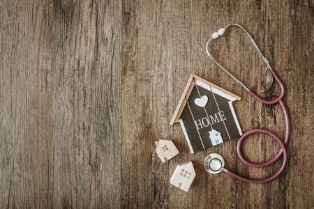 House model with stethoscope on wooden background. Home checking concept
