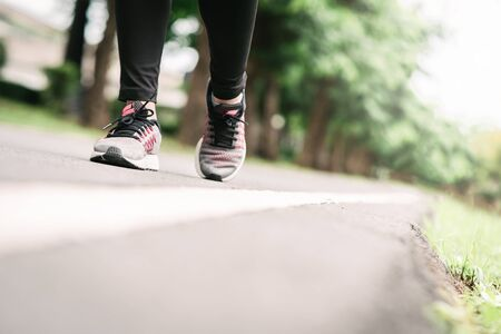 Close up shot of woman runner feet running on road in the park