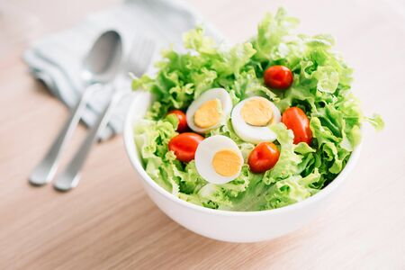 Home made healhty salad bowl with lettuce, red cherry tomatos and eggs on table 写真素材