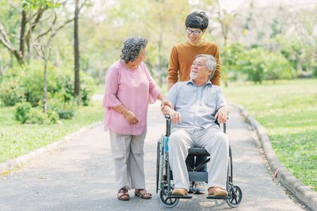 Happy senior Asian man in wheelchair with his wife and son walking in park. aging society concept. Imagens