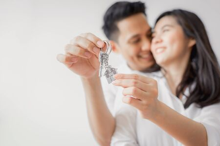 Happy Asian couple embracing and showing key to new home