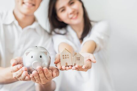 Cropped shot of happy Asian couple holding piggy bank and wooden house models. Saving money for buying new house concept 写真素材