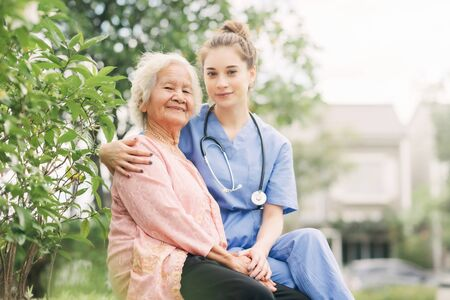 Portrait of a female caregiver nurse care for an Asian elderly woman patient outdoor Stockfoto - 132136308