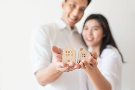 Happy Asian couple in love showing wooden house model. Moving to new house or strating new family life concept..