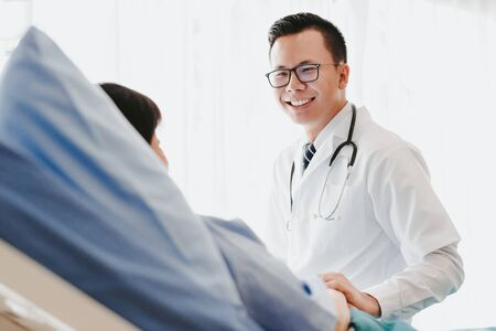 Asian doctor giving his female patient a thorough checkup during his consultation on the bed in hospital
