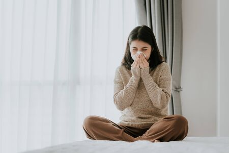 Sick Asian woman using a tissue to sneeze in while setting on the bed at home